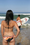 Woman watching a man with a surfboard