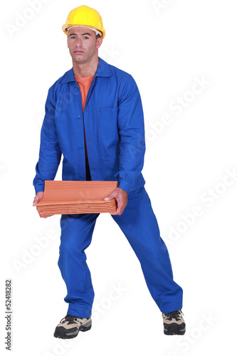 A roofer carrying tiles roof.