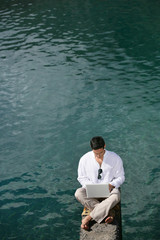 Man with laptop near a lake