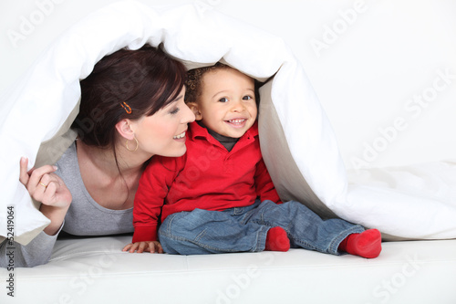 mother and son playing under the blanket