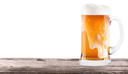 Frosty fresh beer  with foam isolated  on wooden table