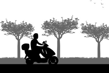 A silhouette of a man on motorcycle who drives along the road