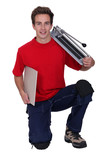 young handyman posing with a tile cutter and a tile