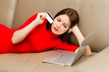 Beautiful woman lying on the sofa with laptop.
