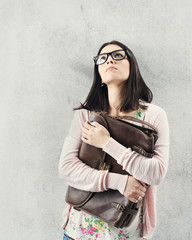 Thoughtful woman in eyeglasses holding bag. teenager problem