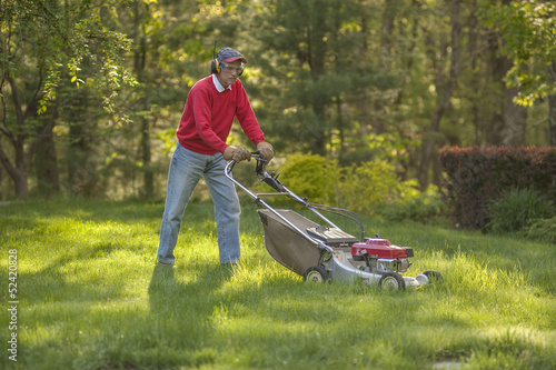 Man mowing the grass in his yard
