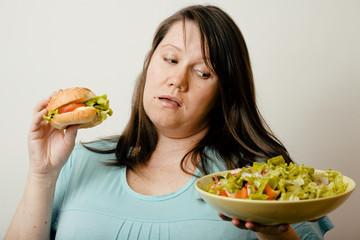 fat white woman having choise between hamburger and salad