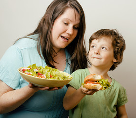 fat woman holding salad and little cute boy with hamburger