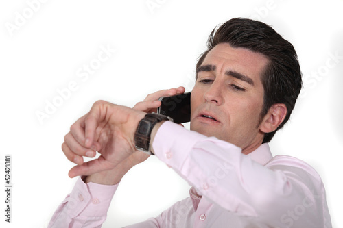 businessman talking on his cell and looking at his watch