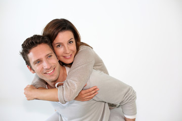 Handsome guy giving piggyback ride to girlfriend
