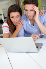 Couple looking at bank account with shocked expression