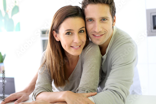 Portrait of cheerful couple standing at home