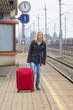 Frau wartet auf Bahnhof auf ihren Zug