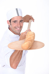 Baker pulling a freshly baked baguette out from the oven