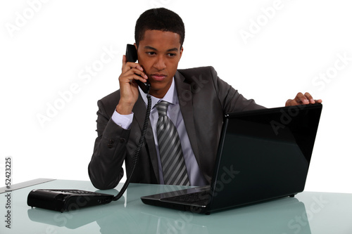 Executive with a phone and laptop