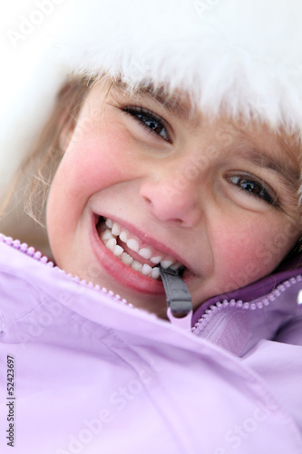 Little girl stood outdoors in winter clothing