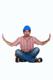 Surprised laborer sitting on white background