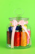 Glass jar containing various colored thread on green background
