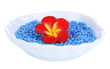 Colorful beads with handmade flower in plate isolated on white