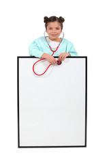 A little girl playing at being a doctor.