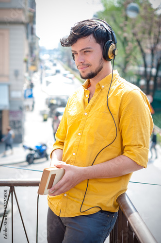 young man reading book and listening music