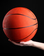 Basketball in woman hand on black background