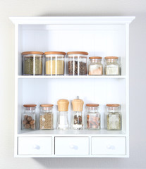 Beautiful white shelves with spices in glass bottles