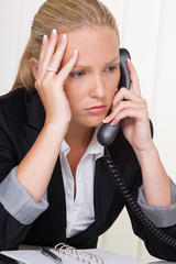 frustrierte Frau mit Telefon im Büro
