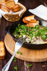 scrambled eggs with herbs and mushrooms in a pan