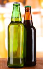 Bier in bottles on table on room background