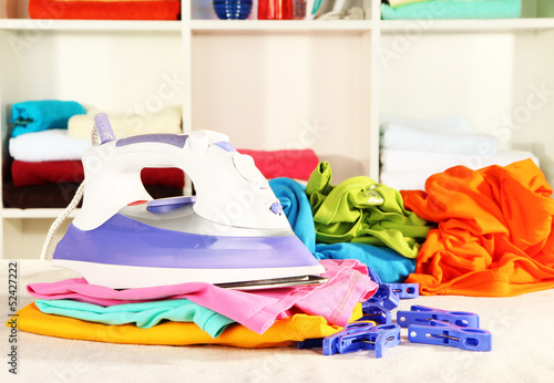 Clothes and iron on table on shelves background - 52427222