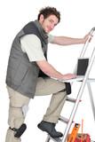 Handyman stood with laptop