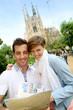 Couple reading travel guide by the sagrada familia church