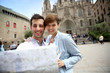 Couple looking at touristic map by Barcelona Cathedral