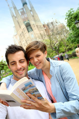 Couple reading travel guide by the sagrada familia church