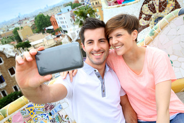 Couple taking picture of themselves in Guell park