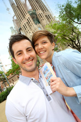 Cheerful couple with travel guide in Barcelona