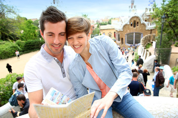 Couple in Barcelona reading travel guide