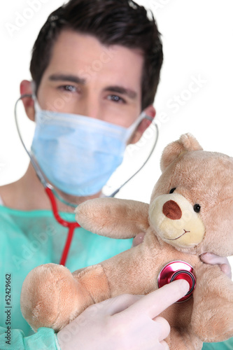 doctor listening to teddy bear heartbeat