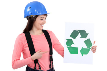 Builder pointing to recycle sign