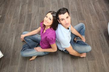 Couple sat on laminate flooring