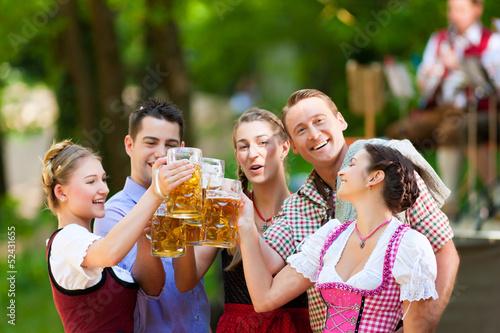 Leinwandbild Motiv Im Biergarten - Freunde trinken Bier in Bayern