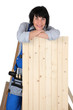 Woman carpenter leaning on a plank