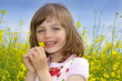 happy little girl with rapeseed flower
