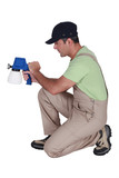 Man using paint spraying device