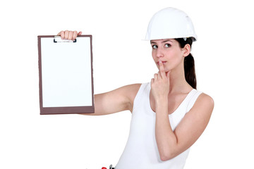 Woman with clip-board making shush gesture