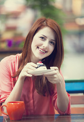 Style redhead girl with cake and cup