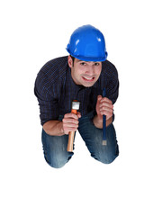 Nervous woodworker holding hammer and chisel