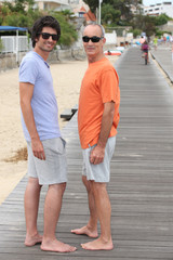 Grandfather and grandson walking along the beach