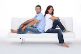 Couple back to back on white sofa